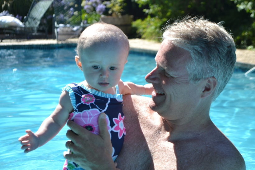 Playing in the pool -- a little terrified of cold water.